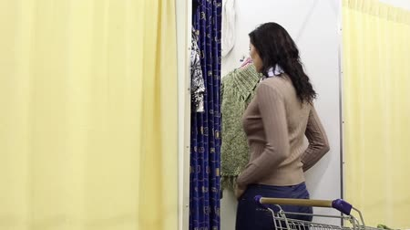 dressing room : Girl Measures New Sweater In Dressing Room