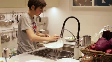 eleven people : Teenager Boy Washing Dishes in the Sink Stock Footage