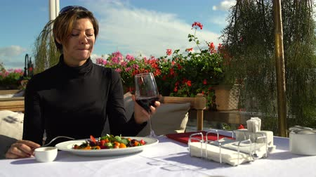 seçkin : Woman drinking a glass of red wine on the terrace of the restaurant