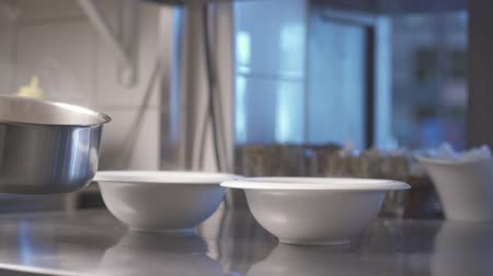 plating food : The chef of restaurant spills the soup bowls.