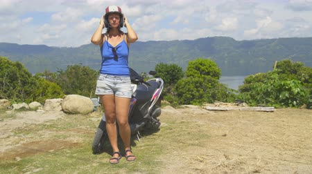 mobilet : A woman puts on a helmet and sunglasses for a trip on a scooter Stok Video