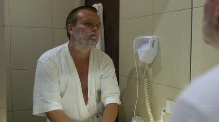 shaving foam : The man in front of a mirror causes shaving foam and shaves machine Stock Footage