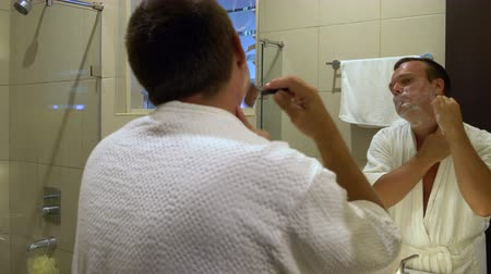 shaving foam : Man shaves machine in front of the mirror