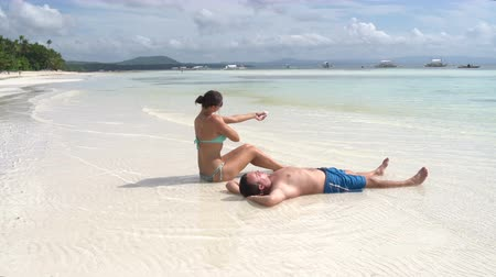 chaise longue : Man sunning at the beach. Woman is smeared with sunscreen