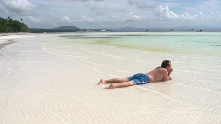 tranquilo : The man lies on his stomach in the sea near the shore