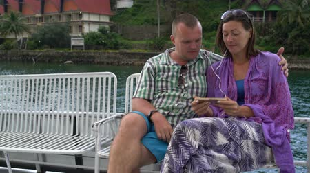remoção : Man and woman listening to music sitting on a bench on a pleasure boat