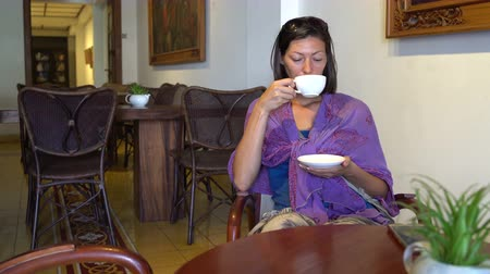 питьевой : Woman drinking coffee while sitting at a table in a cafe