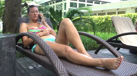 slunečník : Woman in a bathing suit lies in a lounge chair and talking on the phone