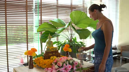 áldás : Songkran. The Thai new year. Girl watering a Buddha statue with water and jasmine petals