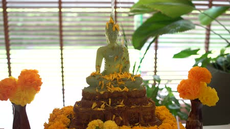yasemin : Buddhist Songkran. Female hand pours a Buddha statue with water and jasmine petals