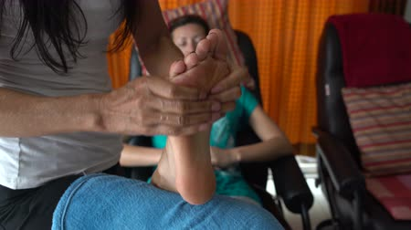 akupresura : Thai foot massage. The masseuse massages a womans foot. A woman relaxes sitting in a chair.