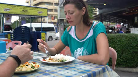 poke : Street food. A woman and man is sitting at a table and eating rice with stewed vegetables Stock Footage