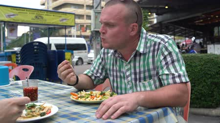 avocado : Street food. A man and a woman are sitting at a table and eating stewed vegetables