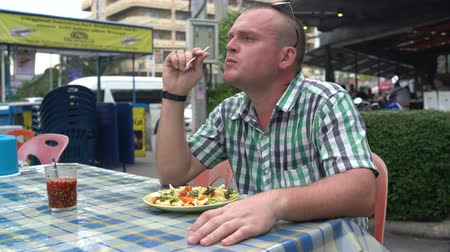 poke : Street food. A man is sitting at a table and eating stewed vegetables Stock Footage