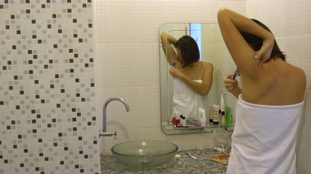 underarm : A woman in a towel shaves her armpits with a razor in front of a mirror in the bathroom
