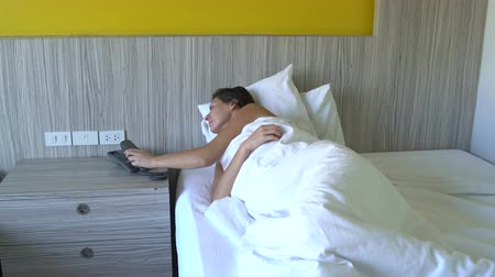 mluvení : A woman calls to phone lying in bed