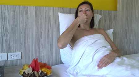 йогурт : Woman eating mango and pineapple lying in bed