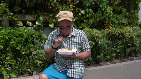 andarilho : Man eats on the streets from the container