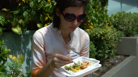 andarilho : Street food. A woman sitting on the street on a parapet eating stewed vegetables from a container