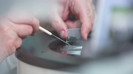 faculty : The microscope slide is coated with a preparation for examination Stock Footage