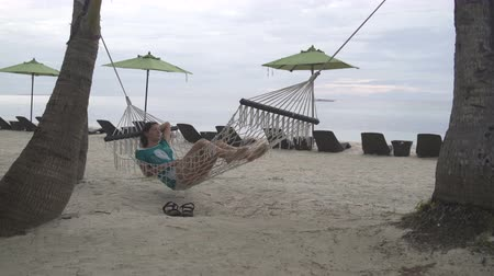buldog : Woman is lying in a hammock on the sea shore in the evening