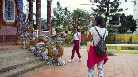heykel : Women are photographed with a dragon statue Stok Video