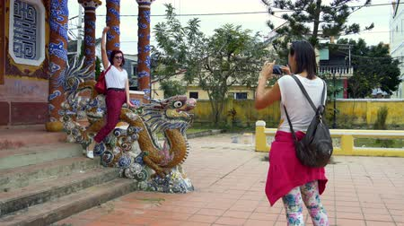 slovinsko : A girl is taking pictures of a woman sitting on a dragon statue