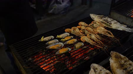 midye : On the barbecue grilled mussels, shrimps and fish. Male hands place mussels in cheese