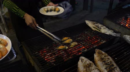 małże : Mens hands remove mussels from the grill on the plate with the help of tongs