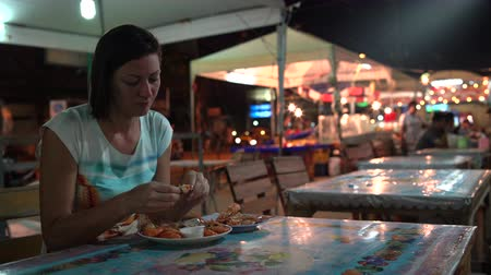 toalha de mesa : A woman is wetting a shrimp in a sauce and eating. Street food Stock Footage