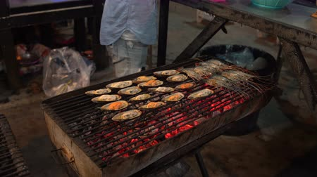 citron : Mens hands lay the shrimp on the barbecue grill. On the barbecue grilled mussels