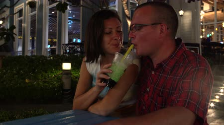 tapioca : A woman and a man are sitting at a table in the street drinking Bubble Tea and kissing
