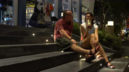 tapioca : A man and a woman are drinking Bubble Tea sitting on the steps of a shopping center and kissing
