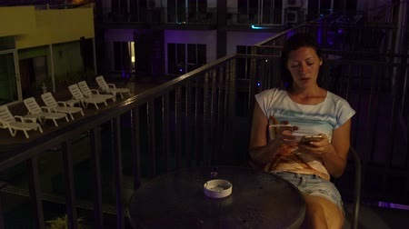 ninhada : A woman sits with a smartphone at a table on the balcony in a hotel room and smokes