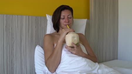 colchão : Woman lying in bed drinking through a tube coconut milk from a young coconut