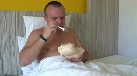 incir : Man lies in bed eating a young coconut with a spoon Stok Video