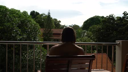 booking : Woman sitting on the hotel balcony