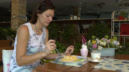 poke : A woman is sitting at a table in a restaurant and eating khao phat