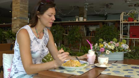 quiche : A woman sits at a table in a restaurant eating khao phat and drinking a milkshake