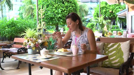 quiche : Woman sits at a table in a restaurant eating khao phat and drinking a milkshake
