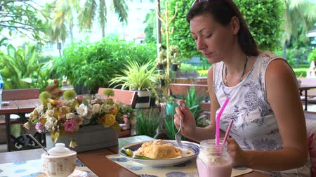 poke : A woman eats khao phat sitting at a table in a restaurant Stock Footage