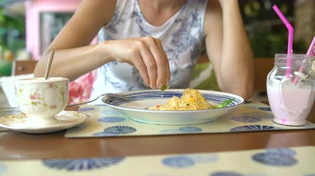 villa : Womans hand squeezes lime on khao phat while sitting at a table in a restaurant