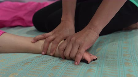 akupresura : Thai massage. A woman is lying on the bed. The masseuse massages a womans foot.