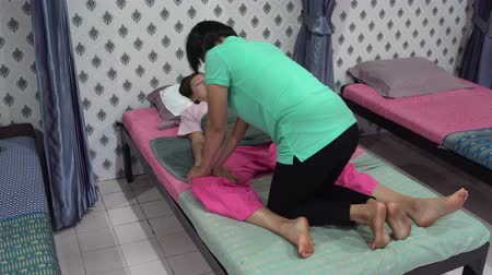 akupresura : Thai massage. A woman is lying on the bed. The masseuse massages the womans thigh.