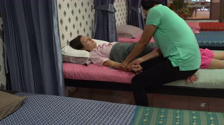 cabeçalho : Thai massage. The masseuse massages a womans hand. A woman is lying on the bed. Vídeos