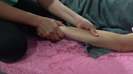 cabeçalho : A woman is lying on the bed. The masseuse kneads the womans hand. Thai massage Vídeos