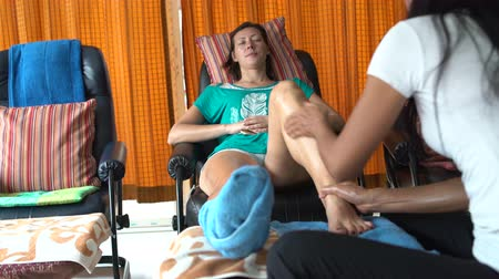 akupresura : Thai foot massage. Masseuse massages a womans leg. A woman is resting sitting in a chair. Wideo