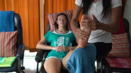 akupresura : Thai foot massage. The masseuse massages a womans foot. A woman is resting sitting in a chair.
