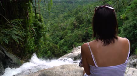 blurring : The woman sits on top of the waterfall and look down