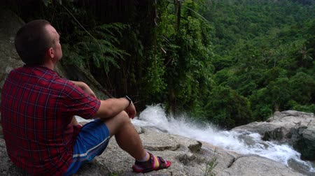 Ванкувер : A man sits at the bottom of a waterfall and looks down